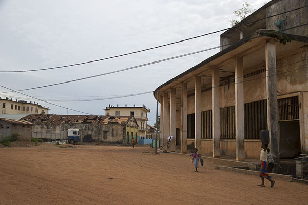 Picture of Main street of Sassandra with kids playing near the first BCA buildingSassandra - Ivory Coast