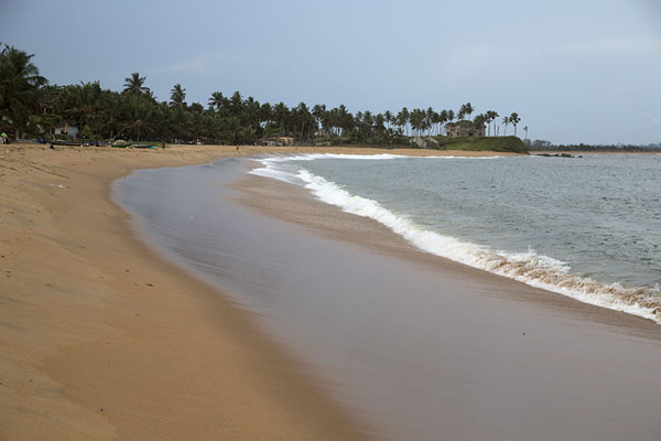 Sassandra beach with the ruins of the governor's house at the far end | Sassandra | Ivory Coast