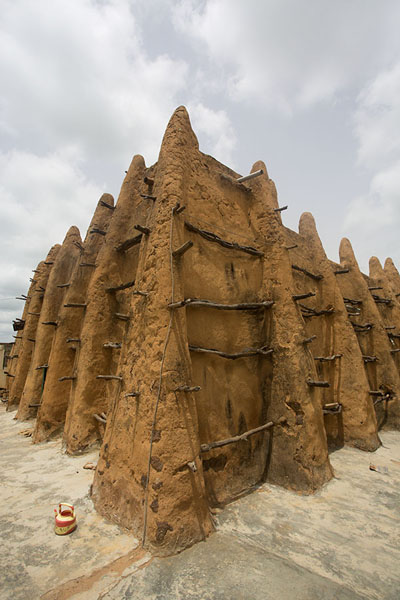 Foto van The adobe mosque of Sorobango with ribbed walls and wooden beams sticking out - Ivoorkust - Afrika