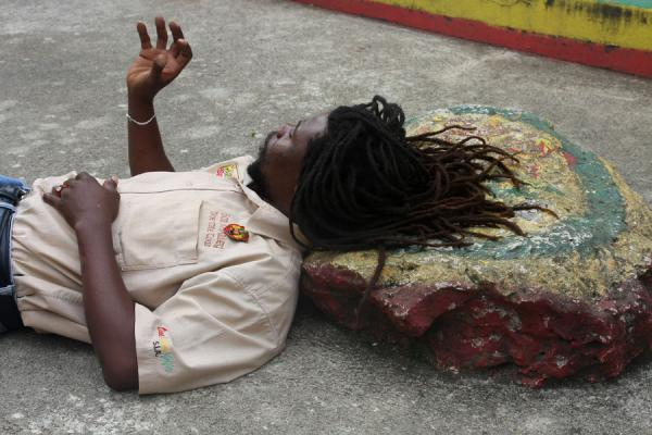 Guide resting his head on the rock pillow, used by Bob for inspiration | Mausolée Bob Marley | Jamaique