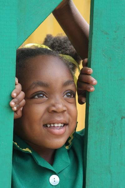 Picture of Jamaican school girl looking through the fence of her school