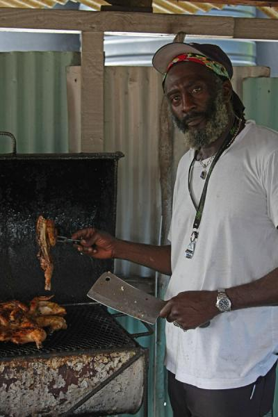 Friendly cook preparing Jamaican chicken jerk | Jamaican people | Jamaica