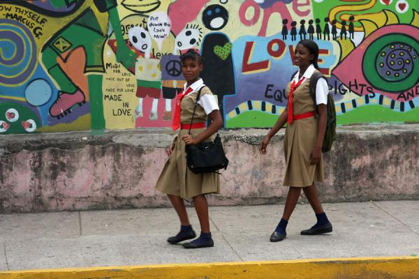 Schoolgirls passing a wall with street art | Jamaicanos | Jamaica