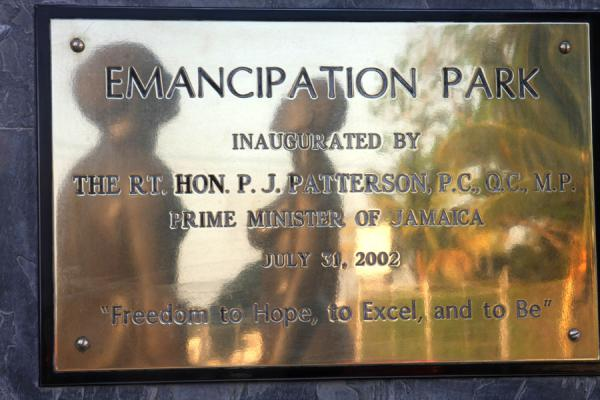 Picture of Redemption Song statue reflected in sign at one of the entrances of Emancipation Park