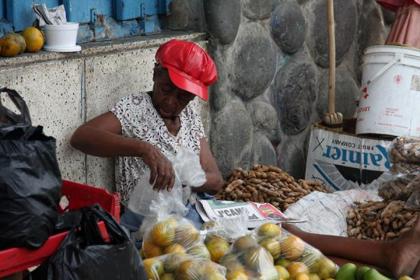 Woman with red cap selling fruit at the market of Kingston | Mercato di Kingston | Giamaica