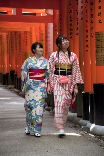 Picture of Two Japanese girls dressed in traditional clothes walking in a tunnel of torii gatesKyoto - Japan