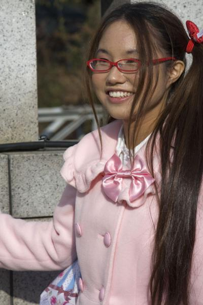 Picture of Harajuku Cosplay (Japan): Japanese girl dressed up in pink posing on Jingu Bridge