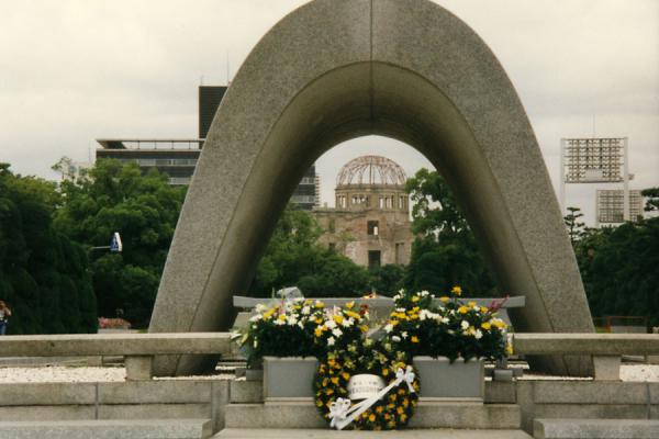 The Atomic bomb dome, Genbaku Dome, or simply A-bomb dome with flowers at the Memorial Cenotaph | Peace Memorial Park | Japan