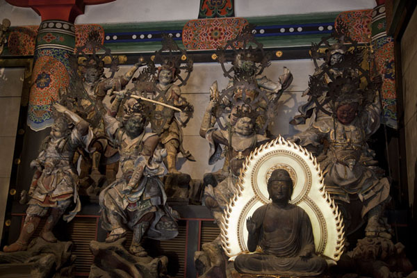 Statues of guardian warriors and a Buddha inside the Kondo, flanking a statue of Yakushi Nyorai | Templo Jingo-ji | Japón