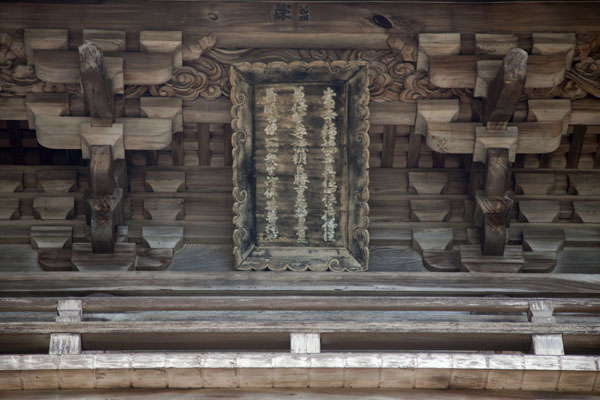 Close-up of wooden slate with text on the outside of a wooden building | Temple Jingo-ji | Japon