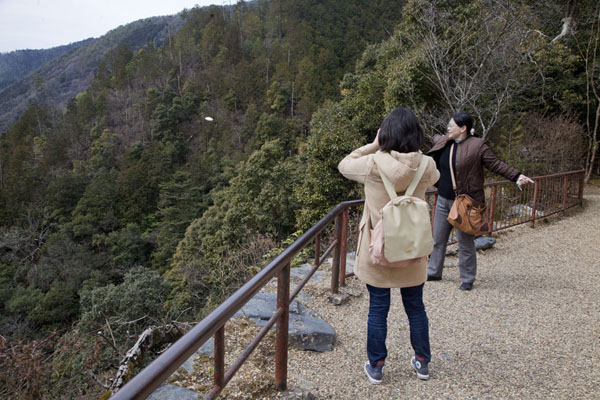 Japanese woman throwing a kawarakenage into Kiyotaki valley below to rid herself of bad karma | Jingo-ji temple | Japan