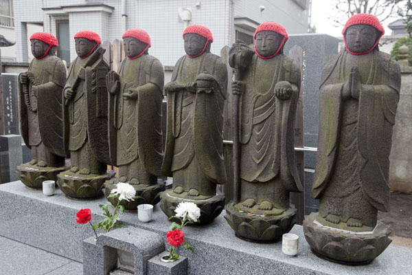 Row of Buddhist statues with red caps at Kannon-ji Temple | Nippori | Japan