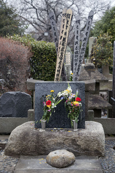 Foto van Tomb with flowers and wooden sticks at Yanaka cemeteryTokyo - Japan