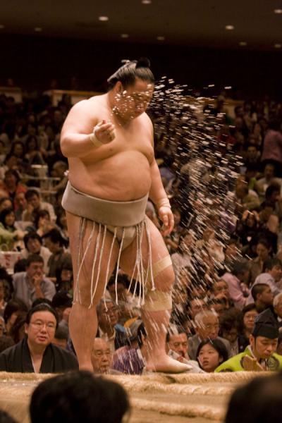Foto di Sumo wrestler throwing salt over the dohyo before his matchTokio - Giappone