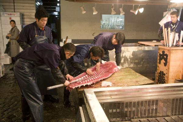 Japanese men cutting through a tuna with an orochi hocho | Tsukiji Central Fish Market | Japan
