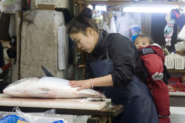 Japanese woman with baby cutting up a fish at Tsukiji market | Tsukiji Central Fish Market | Japan