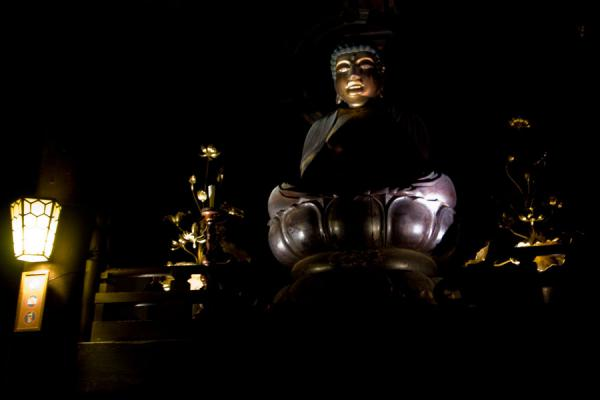 Picture of Buddha statue inside the dark Zenko-ji Temple