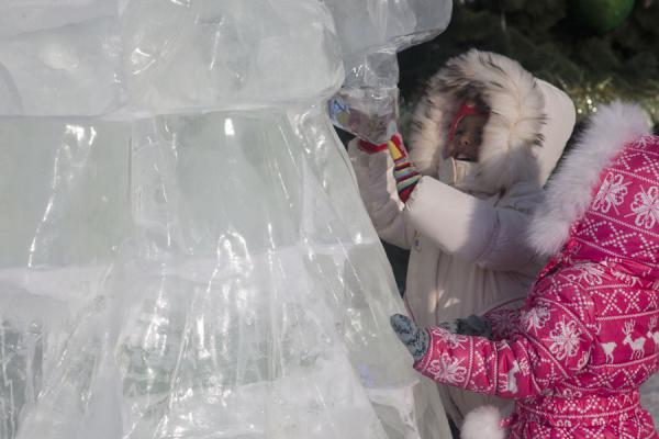 Foto van Two Kazakh girls playing with an ice sculpture in the sculpture park in AstanaAstana - Kazakhstan