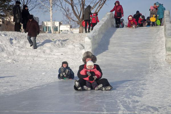 Kids and adults gliding down one of the many ice slide | Astana Ice Sculptures | Kazakhstan