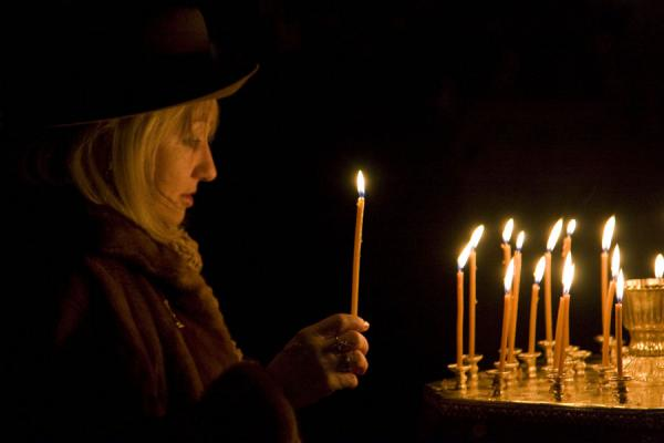 Woman lighting a candle in the Cathedral of the Holy Ascension | Holy Ascension Cathedral | Kazakhstan