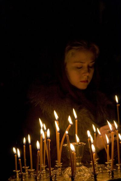 Foto di Woman lighting a candle inside the Cathedral of the Holy AscensionCattedrale della Santa Ascensione - Kazachistan