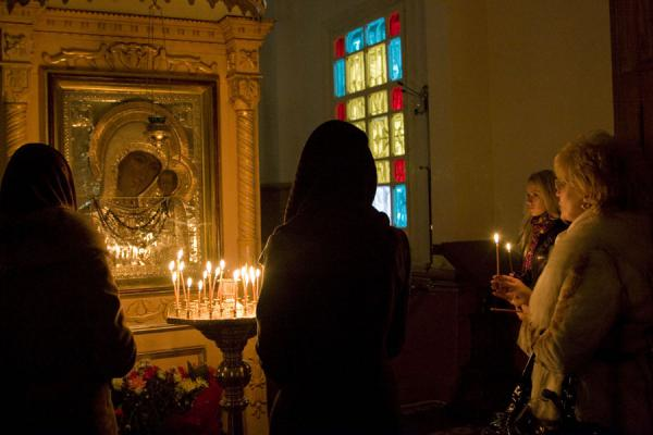Woman lighting candles and praying | Holy Ascension Cathedral | Kazakhstan