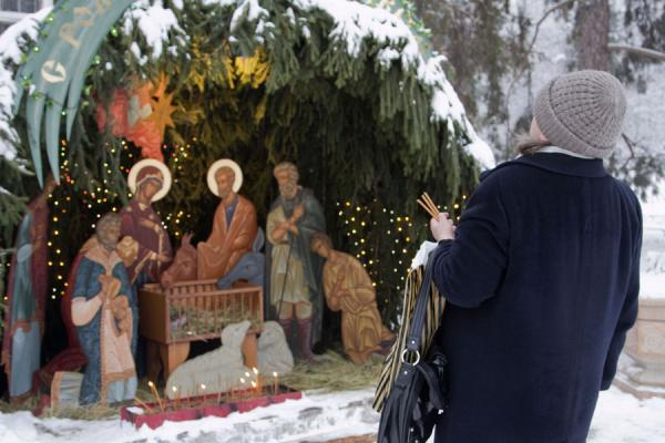 Woman with candles in front of the Nativity scene | Holy Ascension Cathedral | Kazakhstan