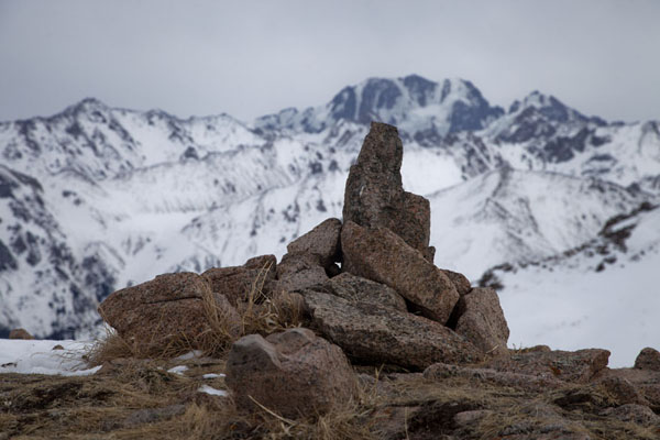 Picture of Pik Talgar, the highest peak of the Trans-Ili Alatau mountains, appears behind a stone marker