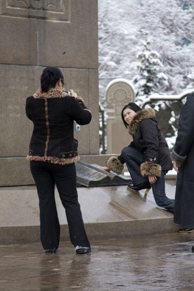 Picture of Kazakh women posing with the bronze book representing the constitution