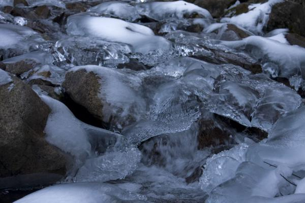 Stream flowing through an icy tunnel | Kim-Asar hiking | Kazakhstan