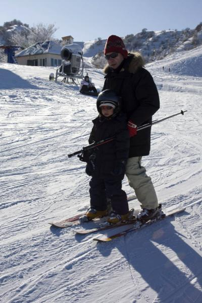 Picture of Kazakh kid skiing between the legs of his father
