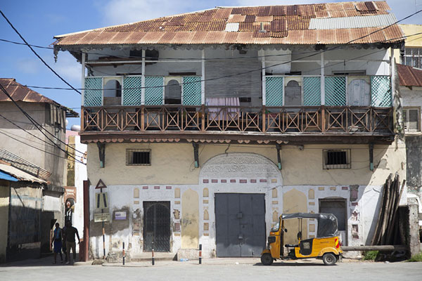 View of Government Square with balconied building and parked rickshaw | Ciudad vieja de Mombasa | Kenia