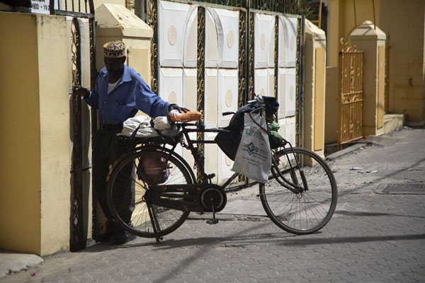 Man with bike closing a door | Città vecchia di Mombasa | Kenya