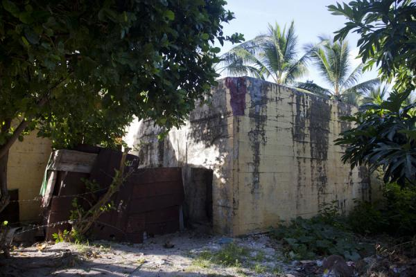 Yellow-painted bunker surrounded by houses in Betio | Battle of Tarawa relics | Kiribati