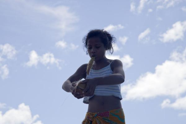 Girl on North Tarawa getting rid of the husk of a coconut with her teeth | I-Kiribati people | Kiribati