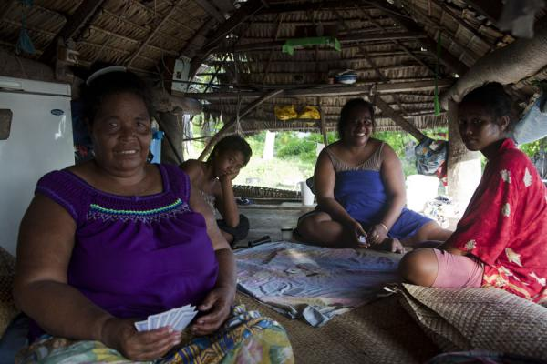 Family in a traditional style thatched hut on North Tarawa | I-Kiribati people | Kiribati