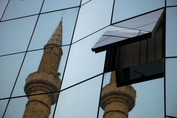 Minaret of Carshi mosque mirrored in the adjacent modern steel and glass highrise tower | Pristina | Kosovo