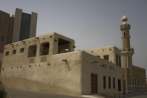 Adobe Beit Khalid contrasting with surrounding modern buildings - 科威特
