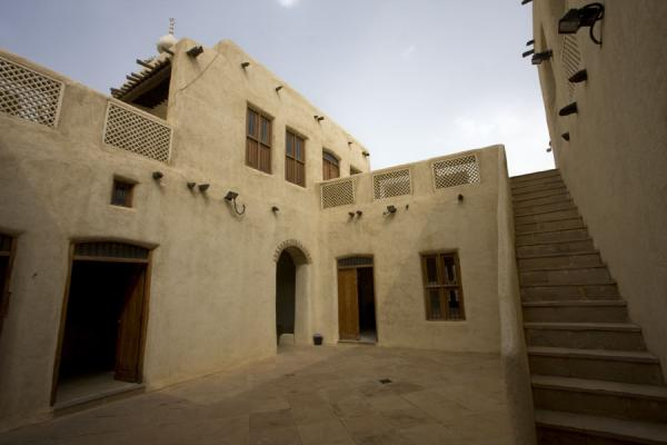 Courtyard of Beit Khalid with stairs, wooden doors and window shutters, and adobe walls | Beit Khalid | Kuwait