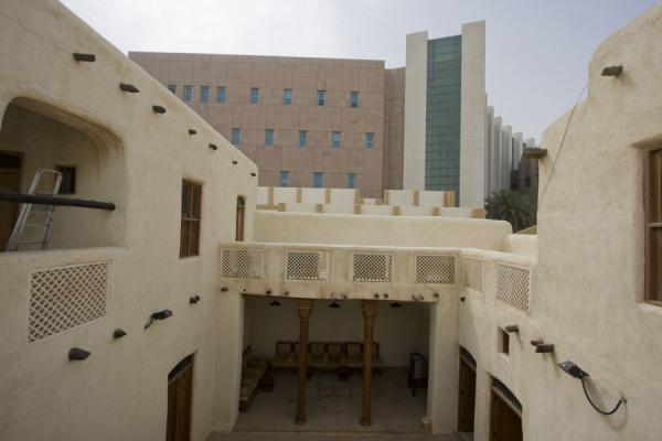 Picture of Beit Khalid (Kuwait): The courtyard of adobe Beit Khalid with modern concrete buildings in the background