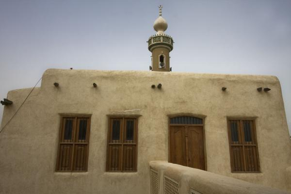 Adobe wall with wooden window shutters on the second floor of Beit Khalid | Beit Khalid | Kuwait