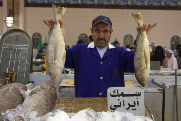 Foto van Holding two of his fish to show off: market vendor at the fish suq - Koeweit - Azië