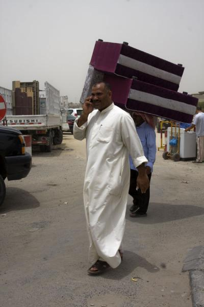 Porter carrying newly-bought sofa with the new owner on the phone | Kuwait Friday Suq | Kuwait