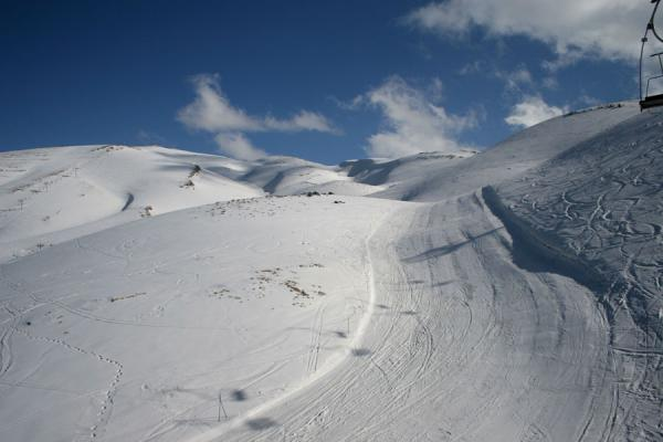 Seen from a ski lift: looking up towards the snowy mountains | Faraya Mzaar Skiing | Lebanon