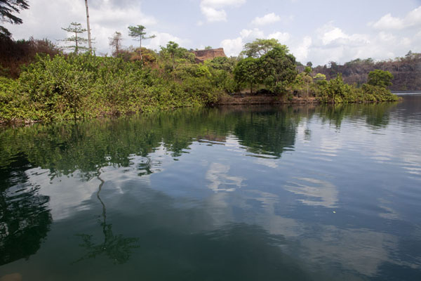 Lush vegetation reflected in the deep waters of Blue Lake | Blue Lake Bomi | Liberia