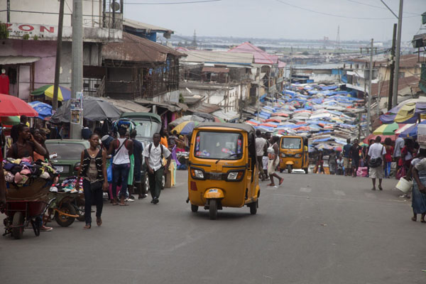 Picture of Rickshaw in downtown Monrovia with a covered street market in the background
