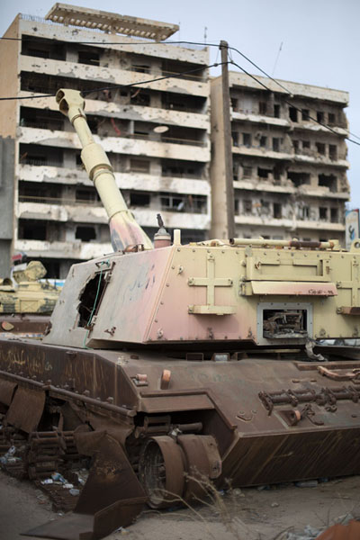 Tank with destroyed buildings in the background: outside the war museum | Misurata museo de la guerra | Libia