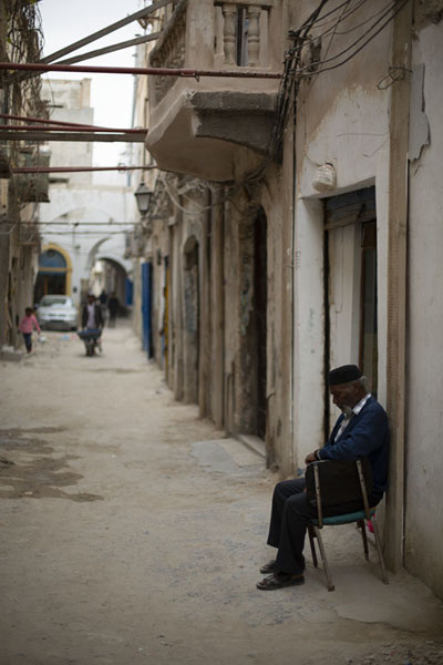 Man sitting outside his house in the old part of Tripoli | Oud Tripoli | Libië