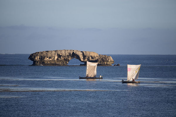 Pirogues sailing by one of the rocky islets on their way to the open sea | Andavadoaka | Madagascar