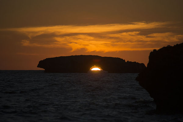 Sun setting through an arch in one of the rocky islets | Andavadoaka | 马达加斯加到